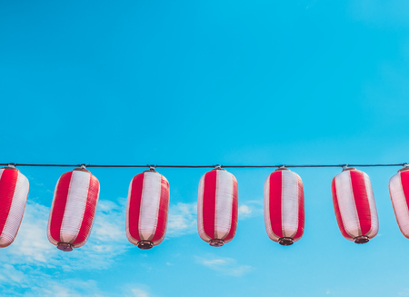 Paper red-white japanese lanterns Chochin hanging on blue sky background. Summer background