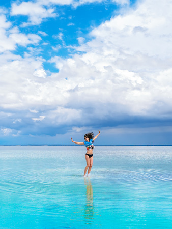 Cheerful bright brunette girl jumps on the water for a photo. A heavenly place, beautiful seascape, clouds on the horizon. Girl in swimsuit makes a jump on salty water of saline