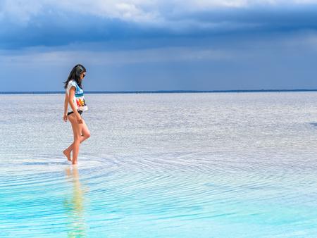 Junge Frau am Strand mit weißen Sand und schönen Landschaft um