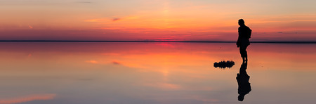 Silhouette of alone man looking toward vibrant sunset reflected in shallow waters of solt lake. Banner size Stock Photo