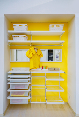 Bright yellow walk -in closet with clothes and shelf, bin, box at home