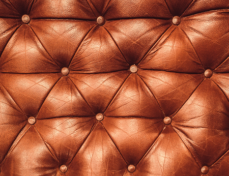 Decorative ginger background of genuine leather. Decorative brown background of genuine leather capitone texture