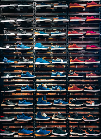 Lots of different sneakers on the showcase on market. Image of sport shoes on shop-window 写真素材
