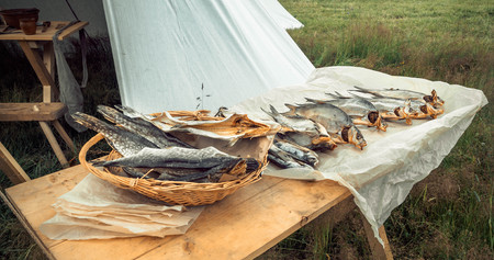 Dried fish on a wooden table on outdoor market.