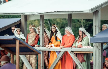 RITTER WEG, MOROZOVO, APRIL 2017: Beautiful ladies in medieval clothes stand in bed watching the tournament of Knights. Historical reconstruction. Redactioneel