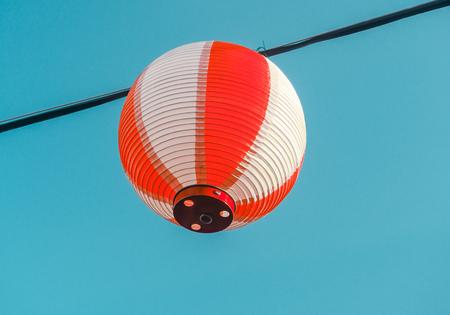 Paper red-white japanese lanterns Chochin hanging on blue sky background Stock Photo - 108011950