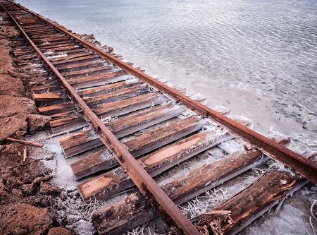 Rusty razy rails and rotten sleepers covered of salt on old railroad tracks on a mound at salt mining lake near brine Stock Photo