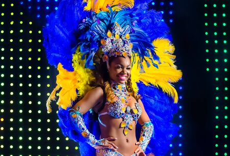 MOSCOW, RUSSIA- MAY 2017: Beautiful girl bright colorful carnival costume dark background. Smiling latin american woman samba dancer blue yellow carnival costume with feathers rhinestones on stage background Редакционное