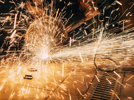 Sparks during cutting of metal angle grinder. A lot of glowing sparks flies around the rotating disk of the grinder. Sparkling background. Metal cutting Фото со стока