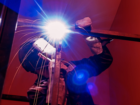 Welder Worker Performs Jump Welding. Worker Welder Performs Arc-Welding Process of Metal Structures. Flying Sparks From the Welding Machine. Welder Welds Metal Profiles for Second Floor Indoors
