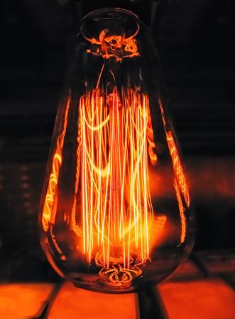 Lampe en verre clair brillant en forme de poire de près. Éclairage edison rétro lampe fond sombre. Ampoule à filament vintage antique.