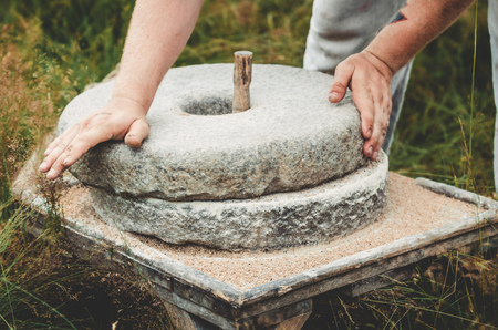 The ancient quern stone hand mill with grain. The man grinds the grain into flour with the help of a millstone. Mens hands on a millstone. Old grinding stones turned by hands