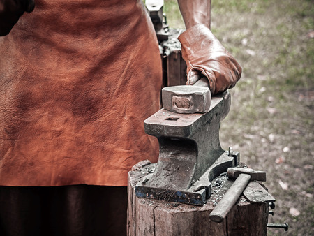 . Blacksmith hand with a hammer on steel anvil . Hand of a blacksmith in leather gloves with hammer close up. The blacksmith in the production process of metal products handmade on the openair workshop Imagens