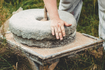 The ancient quern stone hand mill with grain. The man grinds the grain into flour with the help of a millstone. Mens hands on a millstone. Old grinding stones turned by hands Archivio Fotografico