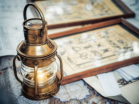 Old brassy ship lantern stands on a map of the seas near pictures with the image of sea knots