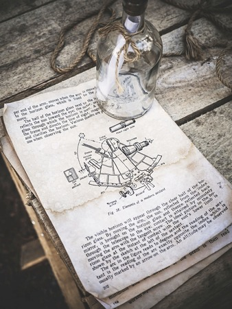 Vintage still life with sextant picture in a old book and empty glass bottle with rope on aged wooden background. The book describes the technique of sextant use in English. Sailing and travel concept top side view