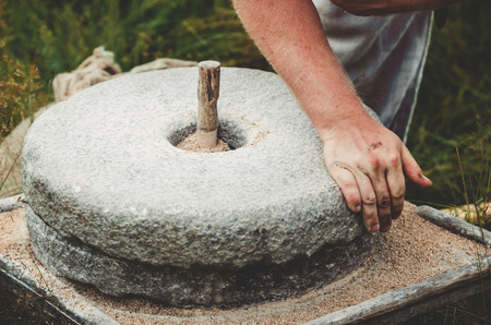 The ancient quern stone hand mill with grain. The man grinds the grain into flour with the help of a millstone. Mens hands on a millstone. Old grinding stones turned by hands Stock Photo