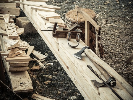 Old woodworking hand tool: wooden plane, chisel ax, and drawing knife in a carpentry workshop on wooden bench ground covered with sawdust background side view