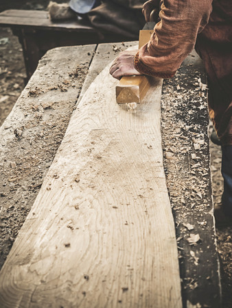 Carpenter in Medieval Cotton Clothes Working With a Wood by Plane. Man Manually Hews a Wooden Board With a Plane. Construction of a wooden bark
