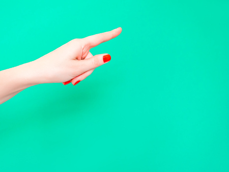 The Hey You Hand Sign. Look At This Sign. Female hand finger pointing isolated on bright turquoise background