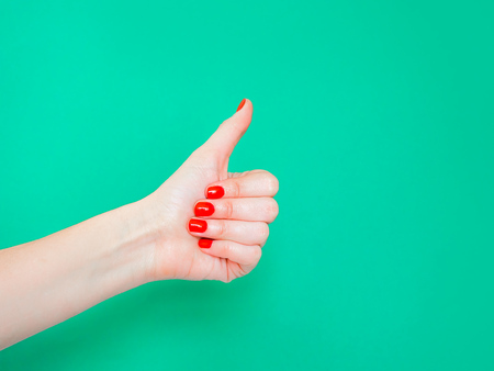 The Thumbs Up Sign. Like Hand Sign. Used when you want to demonstrate that you like something or that you approve of something, The ol thumbs up hand sign. Female hand with red manicure on fingernails holding hand in gesture of likeness giving thumb up on isolated turquoise green color background. 스톡 콘텐츠 - 121632605