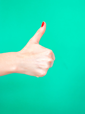 The Thumbs Up Sign. Like Hand Sign. Used when you want to demonstrate that you like something or that you approve of something, The ol thumbs up hand sign. Female hand with red manicure on fingernails holding hand in gesture of likeness giving thumb up on isolated turquoise green color background 스톡 콘텐츠 - 121632607