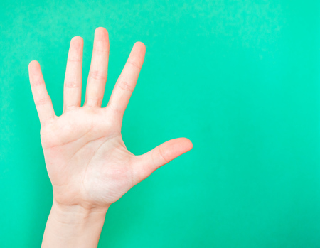Hand showing stop sign. The hand shows the number five. Use the palm of your hand to show when you want something or someone to stop