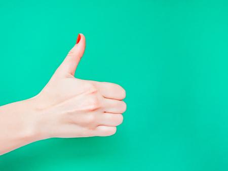 Le signe du pouce levé. Comme le signe de la main. Utilisé lorsque vous voulez démontrer que vous aimez quelque chose ou que vous approuvez quelque chose, le signe de la main du pouce levé. Main féminine avec manucure rouge sur les ongles tenant la main dans un geste de ressemblance abandonnant le pouce sur fond de couleur vert turquoise isolé