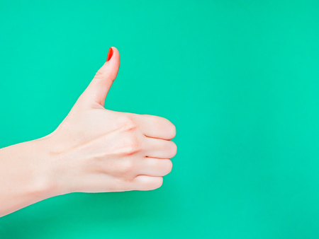 The Thumbs Up Sign. Like Hand Sign. Used when you want to demonstrate that you like something or that you approve of something, The ol thumbs up hand sign. Female hand with red manicure on fingernails holding hand in gesture of likeness giving thumb up on isolated turquoise green color background
