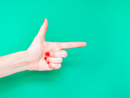 The Finger Gun Hand Sign. Is used as a way to say Yup with your hands. Pointing index finger on isolated turquoise green color background Reklamní fotografie