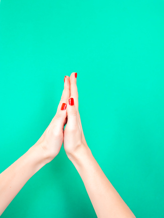 The Thank You Praying Hands Hand Sign. Say thank you with your hands by mimicking the praying hands emoji. Woman hold hands together is symbol prayer and gratitude on isolated turquoise green color background.