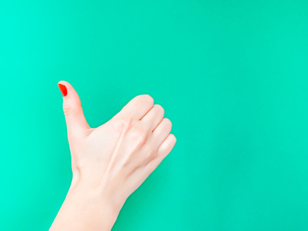 The Thumbs Up Sign. Like Hand Sign. Used when you want to demonstrate that you like something or that you approve of something, The ol thumbs up hand sign. Female hand with red manicure on fingernails holding hand in gesture of likeness giving thumb up on isolated turquoise green color background.