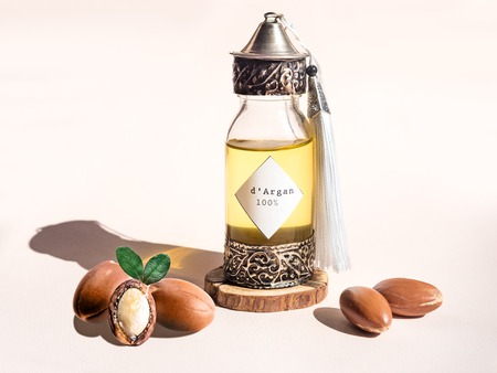 Bouteille décorative avec du fer en relief dans un style marocain traditionnel avec de l'huile d'argan marocaine précieuse et des noix et un éclairage naturel du soleil