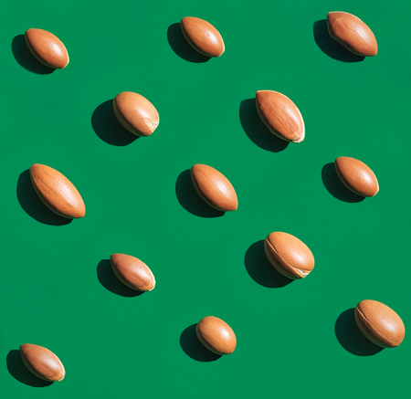 Argan nuts laid out on green background. Natural lighting in direct sunlight. A high resolution