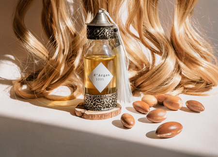 Curls of golden hair and decorative bottle with iron embossed in traditional Moroccan style with precious Moroccan argan oil and nuts ander natural lighting of sun with hadows frame