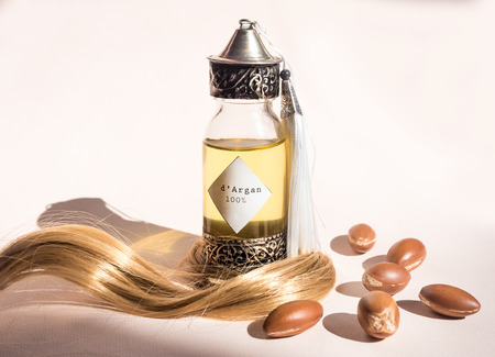 Curll hair of golden hair and decorative bottle with iron embossed in traditional Moroccan style with precious Moroccan argan oil and nuts ander natural lighting of sun