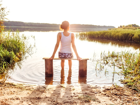 The girl enjoys a beautiful sunset sitting on a bench by the river. Girl sitting near water outdoors. Golden sunset lake. Young woman thinking about something river during golden sunset. Rest by the water. Unity with nature. Lonely girl looks at water Stock Photo