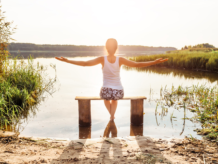 Girl open hands freedom nature. The girl enjoys a beautiful sunset sitting on a bench by the river. Girl sitting near water outdoors. Golden sunset lake. Young woman thinking about something river during golden sunset. Rest by the water. Unity with nature. Lonely girl looks at water