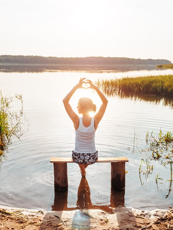 The girl enjoys a beautiful sunset sits on a bench by the river and shows hands fingers heart sign. Girl sitting near water outdoors. Young woman on the river bank during golden sunset. People rest by the water. Unity with nature. Love nature concept