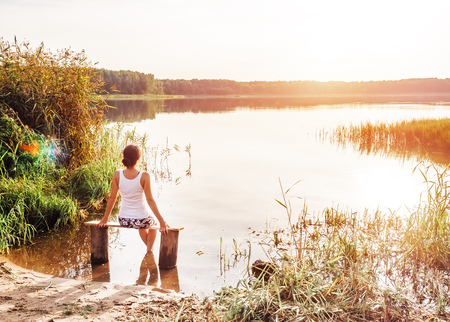 Pensive girl sits on a bench by the river and enjoys a beautiful sunset. Girl sitting near water outdoors. Golden sunset on the lake. Young woman thinking about something near river during amazing sunset. Unity of people with nature