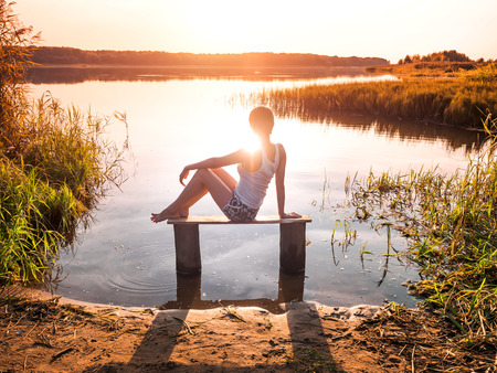 Pensive girl sits on a bench by the river and enjoys a beautiful sunset. Girl sitting near water outdoors sunbeam touches her body. Golden sunset on the lake. Young woman thinking about something near river during amazing sunset. Unity of people with nature