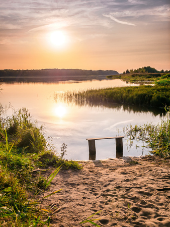 Empty bench near the river at sunset. Away from the hustle and bustle. Sun setting over the horizon. Forest near the Volga River. Beautiful natural background