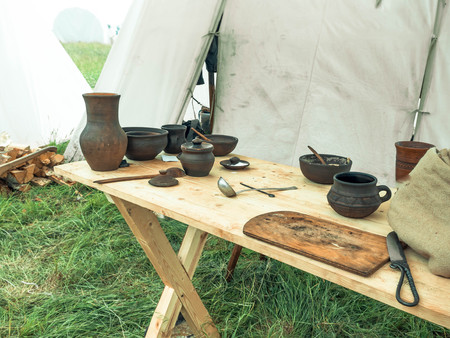 Outdoor scene of medieval way of life. Ancient wooden and clay dishes left on table after dinner Stock Photo