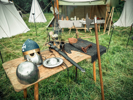 Medieval scene. Medieval knight attributes are helmet, chain mail, shield buckler, sword, halberd. Reconstruction of medieval life