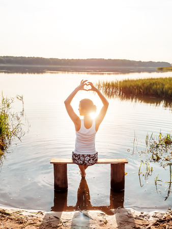 A young girl sits on a bench by the river enjoys a beautiful sunset and shows hands fingers heart sign. Girl sitting near water outdoors. Golden sunset on the lake. Young woman thinking about something near river during amazing sunset. Unity of people with nature. Love of nature concept