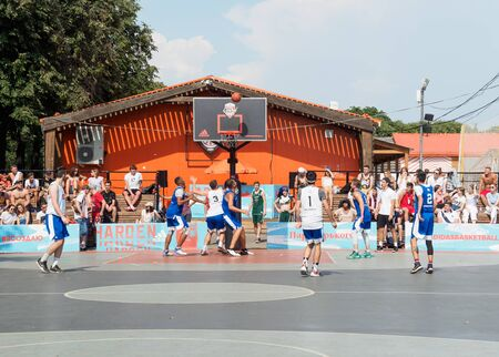 Moscow, Russia - August 4, 2018: Team playing basketball in the Gorky Park in summer. City street youth basketball tournament. Basketball player throws the ball into the basketball hoop