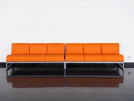 Empty orange sofa in the room near white wall. Waiting hall 스톡 콘텐츠