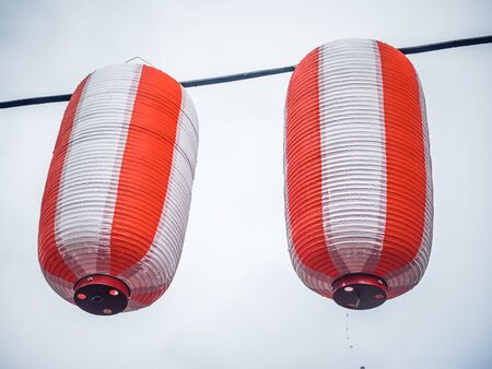 Two paper red-white japanese lanterns Chochin hanging on garland sky background 스톡 콘텐츠