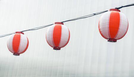 Three round paper red-white japanese lanterns Chochin hanging on garland sky background