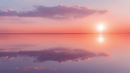 Landscape beautiful lilac sunset red sky solt lake saline Elton Baskunchak. The sun sets behind the horizon. The clouds are like the hands of a man holding the sun. Zen harmony, serenity, tranquility